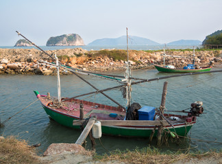 Old fishing boat is docked on the background of the shore rocks and grass