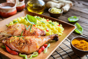 Baked chicken thighs with honey, grated ginger and rice with turmeric on a wooden background
