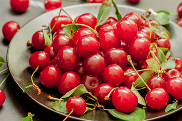 Black plate with delicious, juicy, bright cherries