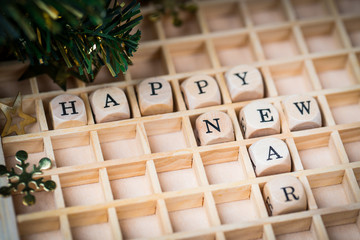 Happy New Year greeting on wooden cubes with  festive greenery in the background