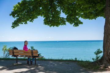 Young beautiful woman sitting on a bench on the lake shore and w