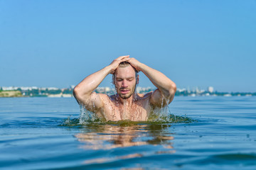 Athletic man out of the water with a wet head