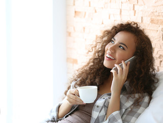 African American woman with a cup of coffee talking on mobile phone