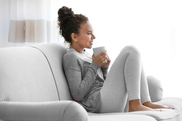 African American woman with a cup of coffee sitting on sofa on window background