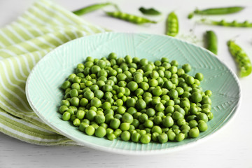 Fresh green peas in plate on napkin