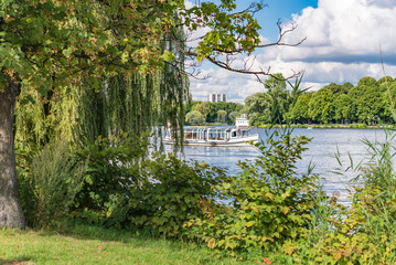 Alster Lake in Hamburg Germany on a summer day. View at beautiful and famous city park Alsterwiese, located in the center of the Hansestadt Hamburg, image for travel concept