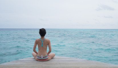 woman with yoga pose in front of a clear aqua ocean in Maldives