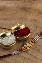 A Rakhi with rice grains and kumkum. An Indian festival Raksha Bandhan background.