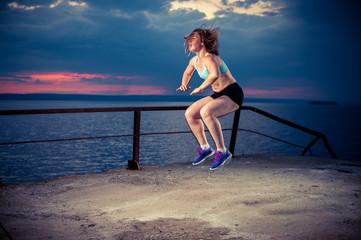 Fit woman in sportswear doing squat jumps