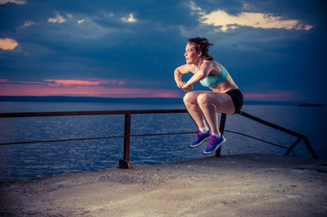 Strong young woman doing plyometric exercises on pier