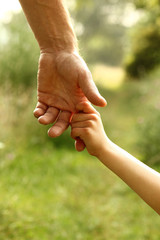 the parent holds the hand of a child