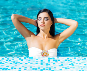 Portrait of a young and sexy woman in a swimming pool