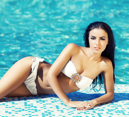 Seductive young woman in a swimsuit posing next to a pool
