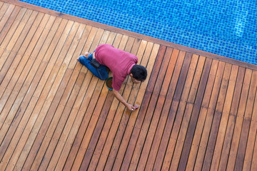 A man painting exterior wooden pool deck, Top view