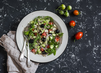 Quinoa and vegetables salad on a dark background. Delicious vegetarian food