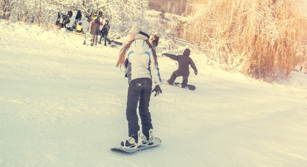 girl on snowboard on snowhill