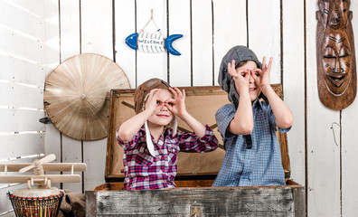 two little kids in pilot hats in big old chest making glasses with hands