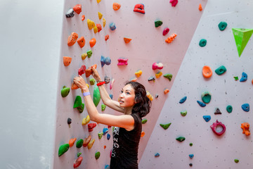 Woman making effort when climbing indoors