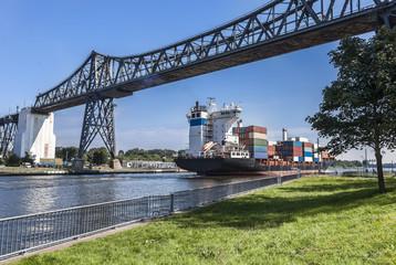 Containerschiff im Nord-Ostsee-Kanal bei Rendsburg unter der historischen Eisenbahnhochbrücke