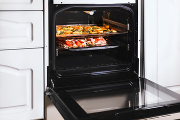 Cooking food on roasting dishes in  hot oven