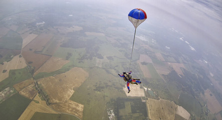 Skydiving tandem parachute above the countryside