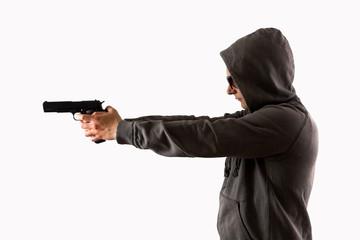 Mann im Kapuzenpullover zielt mit Pistole vor weißem Hintergrund freigestellt
