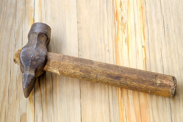 Old hammer on wooden table in center