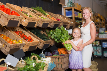 Portrait of young woman and girl buying greens