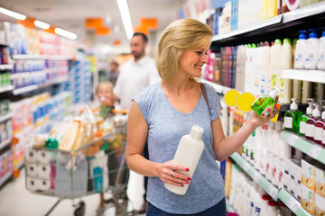 Woman selecting shampoo in supermarket.