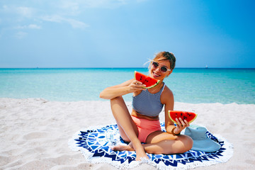 Woman eating watermelon on the beach