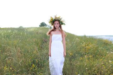 девушка с венком в поле одета в белое платье