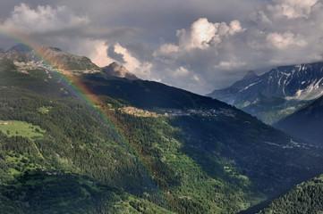 montagne sous ciel nuageux avec arc en ciel