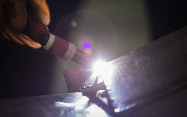 close up of technician welding metal pipe with argon,focus flash