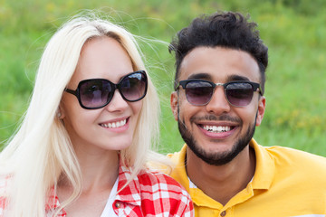 Couple face close up outdoor green grass, mix race man and woman sunglasses
