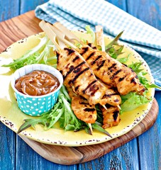 homemade chicken kebabs on wooden skewers with lettuce and peanut sauce