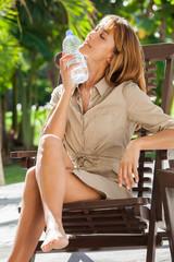 femme dans un jardin qui se rafraichit avec une bouteille froide
