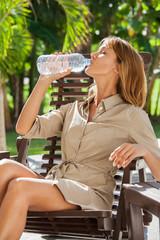 femme dans un jardin qui boit de l'eau