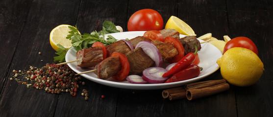 shashlik with vegetables on wooden background