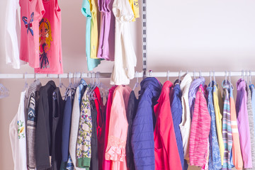 Choice of fashion clothes of different colors in walk-in clothin