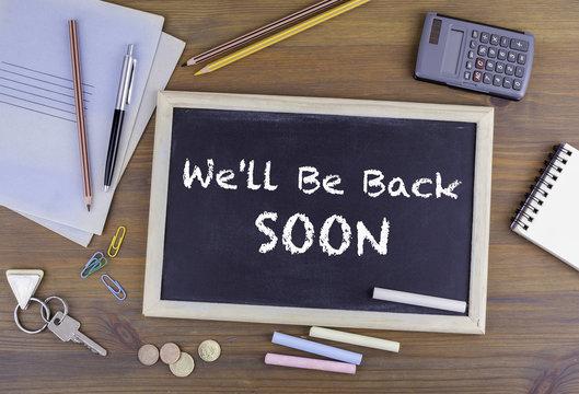 We'll Be Back Soon. Chalkboard on wooden office desk