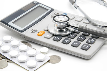 Calculator and stethoscopes on white background