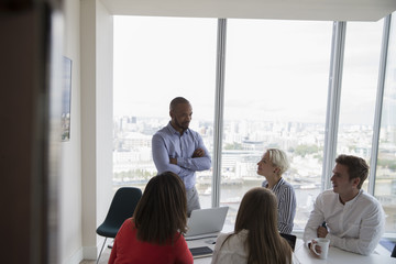 Businessman Addressing Meeting In High Rise Office
