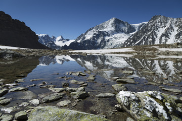 Fotomurales - Mountains reflected in a lake high in the Swiss mountains near Arolla, Wallis.