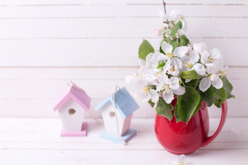 Tender apple tree flowers in white pitcher, two decorative bird