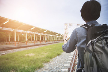 woman holding map with backpack at train station