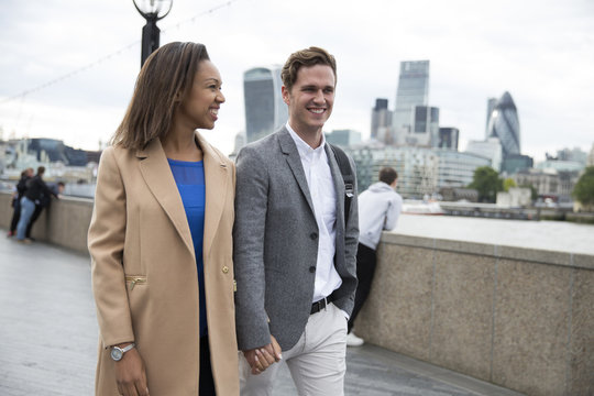 Young Couple Walking To Work With City Skyline In Background