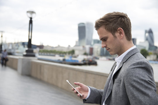 Businessman Checking Mobile Phone Messages On Walk To Work