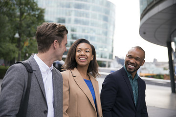 Smiling business people walking outside office building
