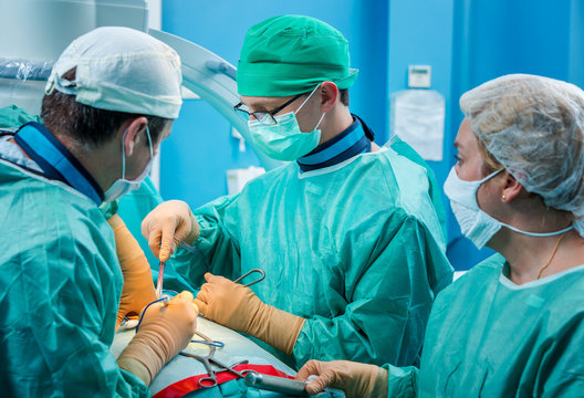Orthopedic surgeons in action, operating a human spine after inj