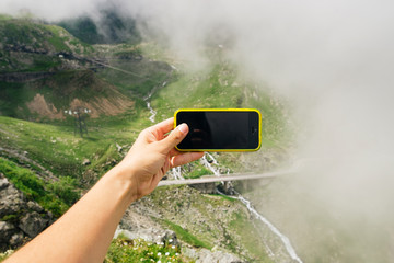 Tourist is using smart phone to take a photo of incredible view of the mountains